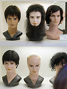 A window display in a Tokyo store of male mannequin heads wearing assorted wigs