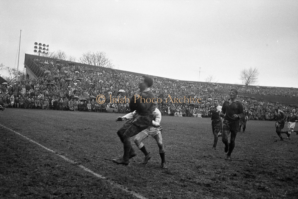 M A English, in possession, tackled by Jackson of England,..Irish Rugby Football Union, Ireland v England, Five Nations, Landsdowne Road, Dublin, Ireland, Saturday 9th February, 1963,.9.2.1963, 2.9.1963,..Referee- H B Laidlaw, Scottish Rugby Union, ..Score- Ireland 0 - 0 England, ..Irish Team, ..B D E Marshall, Wearing number 15 Irish jersey, Full Back, Queens University Rugby Football Club, Belfast, Northern Ireland,..W R Hunter, Wearing number 14 Irish jersey, Right Wing, C I Y M S Rugby Football Club, Belfast, Northern Ireland, ..J C Walsh,  Wearing number 13 Irish jersey, Right Centre, University college Cork Football Club, Cork, Ireland,..P J Casey, Wearing number 12 Irish jersey, Left Centre, University College Dublin Rugby Football Club, Dublin, Ireland, ..N H Brophy, Wearing number 11 Irish jersey, Left wing, Blackrock College Rugby Football Club, Dublin, Ireland, ..M A English, Wearing number 10 Irish jersey, Stand Off, Landsdowne Rugby Football Club, Dublin, Ireland, ..J C Kelly, Wearing number 9 Irish jersey, Scrum Half, University College Dublin Rugby Football Club, Dublin, Ireland,..R J McLoughlin, Wearing number 1 Irish jersey, Forward, Blackrock College Rugby Football Club, Dublin, Ireland, ..A R Dawson, Wearing number 2 Irish jersey, Forward, Wanderers Rugby Football Club, Dublin, Ireland, ..S Millar, Wearing number 3 Irish jersey, Forward, Ballymena Rugby Football Club, Antrim, Northern Ireland,..W A Mulcahy, Wearing number 5 Irish jersey, Captain of the Irish team, Forward, Bective Rangers Rugby Football Club, Dublin, Ireland,  ..W J McBride, Wearing number 5 Irish jersey, Forward, Ballymena Rugby Football Club, Antrim, Northern Ireland,..E P McGuire, Wearing number 6 Irish jersey, Forward, University college Galway Football Club, Galway, Ireland,..C J Dick, Wearing number 8 Irish jersey, Forward, Ballymena Rugby Football Club, Antrim, Northern Ireland,..M D Kiely, Wearing number 7 Irish jersey, Forward, Landsdowne Rugby Football Club, Dublin, Irel