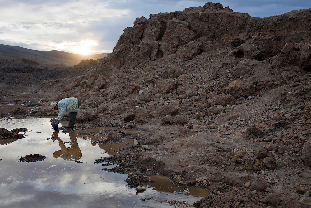 A woman pans for specks of gold next to mounds of excavated hillocks. An estimated one-sixth of Mongolia's population is involved in ninja mining. It brings much-needed cash into the poor rural areas.