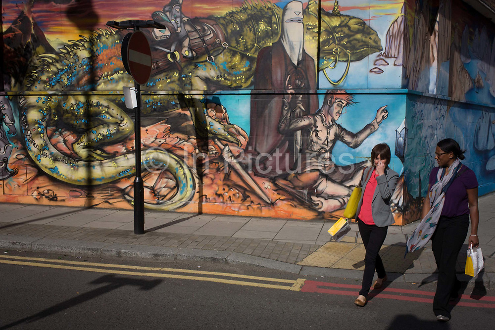 Elaborate wall art in Curtain Street, Shoreditch, East London. Two women have just bought lunch from a nearby cafe and carry their yellow lunch bags across the road, past the large mural that features a fantasy scene of mythical beasts and characters. The murals are temporary, changing regularly so that the art is fresh and surprising.