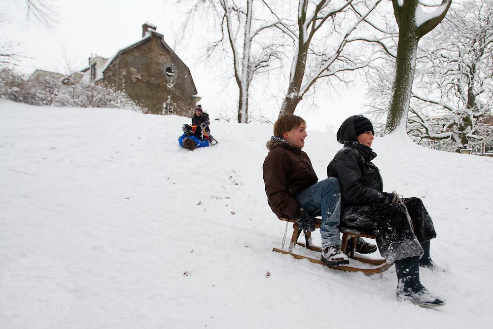 Jongens glijden op een slee de heuvel af in een park in Utrecht.<br /> <br /> Boys on a sled in a park in Utrecht.