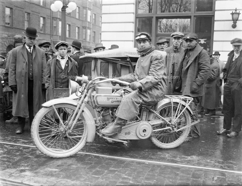 9409-01. Harley Davidson 1915. The Motorcycle & Supply Company had just received the first Harley Davidson Cycle Truck to reach Portland. The three-wheeled vehicle was advertised as being so powerful that it could carry more freight than its own weight. It is shown in front of the Oregon Journal headquarters in the Jackson Tower building on the southeast corner of SW Broadway at Yamhill, Portland. The Portland Hotel, presently the site of Pioneer Courthouse Square, is on the left in the background. January 22, 1915.. see January 24, 1915, page 3, col. 2-3