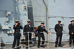 An officer aboard HMS St Albans encourages the crowd as the frigate arrives back at Portsmouth Naval Base following a nine-month deployment to the Middle East.