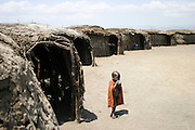 Africa, Tanzania, members of the Datoga tribe a baby stands in front of huts
