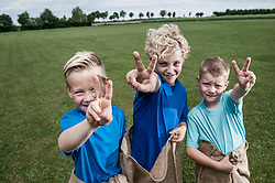 Three young blond boys posing victory sign