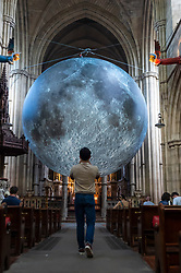 © Licensed to London News Pictures. 19/08/2021. LONDON, UK.  A visitor views Luke Jerram 's Museum of the Moon, a 7m diameter artwork featuring detailed NASA imagery of the lunar surface.  At an approximate 1:500,000 scale, each centimetre of the internally lit sphere represents 5km of the moon's surface. The touring artwork is on display until 30 August at St John the Baptist Church near Shepherd's Bush and forms part of this year's Kensington and Chelsea Festival.  Photo credit: Stephen Chung/LNP
