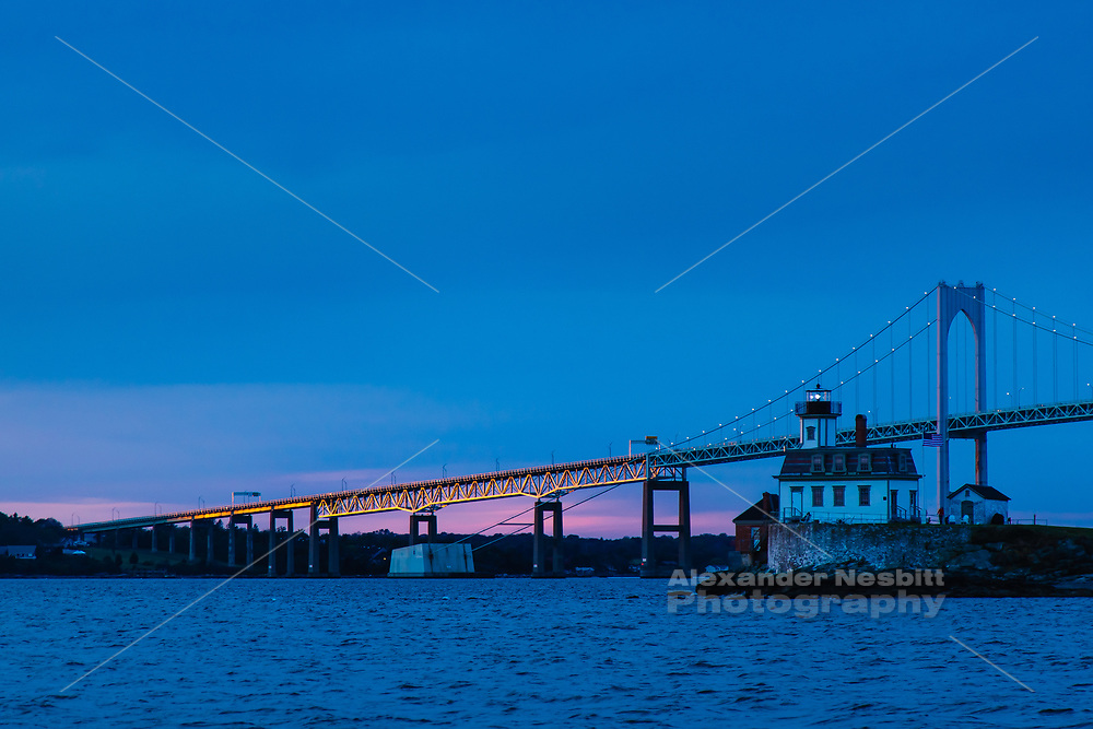 The Newport Bridge catches the last rays of sunset behind the Rode Island Light house