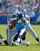 October 30, 2005, Nashville, Tennessee;  Quarterback Steve McNair of the Tennessee Titans runs into the Oakland Raider defense of Jarrod Cooper(40), and Stuart Schweigert(30) as the Titans lose to the Raiders 34-25 at the Coliseum.