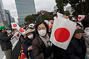 Well-wishers carry Japanese flags  at the Imperial Palace to celebrate the 85th birthday of Emperor Akihito of Japan. The Emperor, who is the son of Japan's wartime leader, Emperor Hirohito, gave a speech to mark his last birthday before his upcoming abdication, saying he felt relief that his reign was coming to an end without having seen his country at war again and that it was important to continue to educate young people about japan's wartime past. Imperial Palace, Tokyo, Japan. Sunday December 23rd 2018