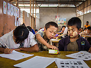 06 MARCH 2014 - MAE SOT, TAK, THAILAND: Students share colored pencils during final exams at the Sky Blue School. There are approximately 140 students in the Sky Blue School, north of Mae Sot. The school is next to the main landfill for Mae Sot and serves the children of the people who work in the landfill. The school relies on grants and donations from Non Governmental Organizations (NGOs). Reforms in Myanmar have alllowed NGOs to operate in Myanmar, as a result many NGOs are shifting resources to operations in Myanmar, leaving Burmese migrants and refugees in Thailand vulnerable. The Sky Blue School was not able to pay its teachers for three months during the current school year because money promised by a NGO wasn't delivered when the NGO started to support schools in Burma. The school got an emergency grant from the Burma Migrant Teachers' Association and has since been able to pay the teachers.      PHOTO BY JACK KURTZ