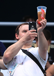 A fan takes a photograph of his drink during the FIFA World Cup Group G match at the Nizhny Novgorod Stadium.