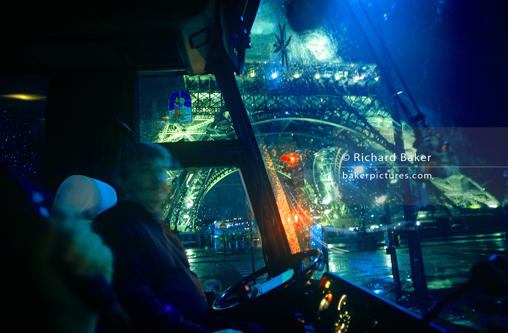 Blurred view of a tourist coach driver as he negotiates the dark wet streets around at Paris' Eiffel Tower.
