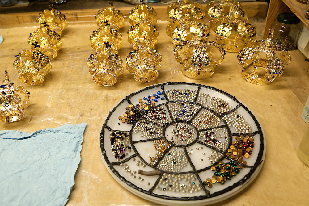 A divided tray of Swarovski crystals waiting to be mounted onto crowns. In the background are finished crowns.