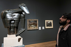 "© Licensed to London News Pictures. 04/06/2018. LONDON, UK. A gallery staff member views ""Torso in metal from The Rock Drill"", 1913-16, by Jacob Epstein at a preview of ""Aftermath:  Art in the wake of World War One"" at Tate Britain.  The exhibition marks 100 years since the end of the First World War, exploring the impact of the conflict on British, German, and French art in over 150 works from 1916 to 1932.  The show runs 5 June to 23 September 2018.  Photo credit: Stephen Chung/LNP"