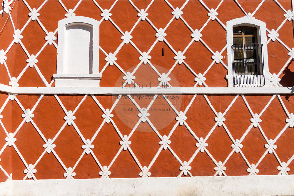 The brightly painted red and white wall of the Town Hall in the beautiful colonial village of Bernal, Queretaro, Mexico. Bernal is a quaint colonial town known for the Pena de Bernal, a giant monolith which dominates the tiny village is the third highest on the planet.