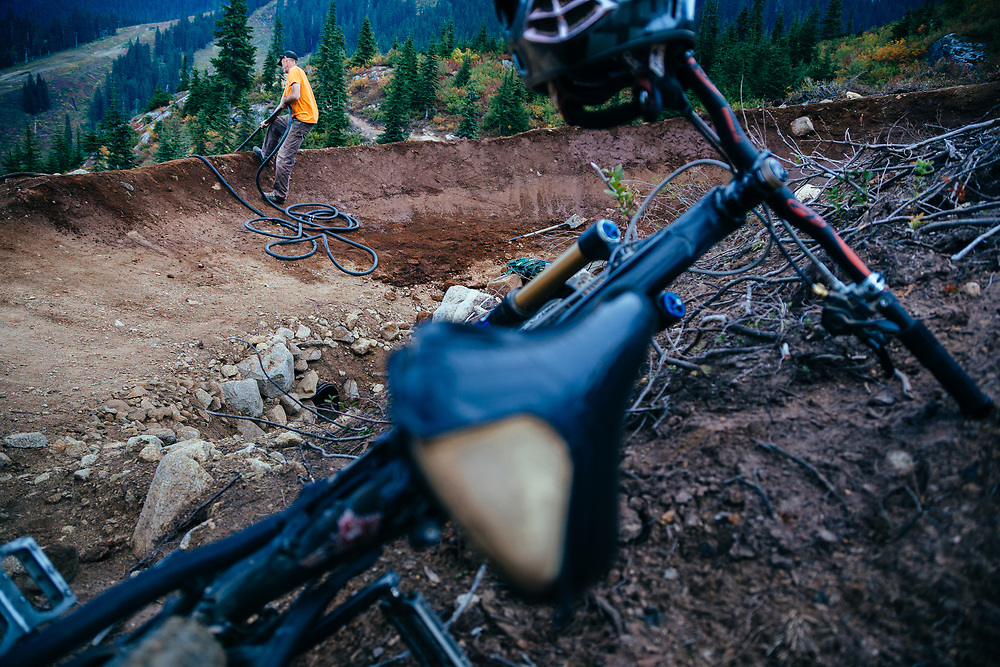 Tall Tim - Trail Building Master pulls up a water hose at Steven's Pass Resort.