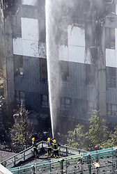 Emergency services spray water towards a fire that engulfed the 24-storey Grenfell Tower in west London.