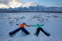 Russell and Jessica Laman (ages 12 and 9) make snow angels below the Tetons.<br />Grand Teton National Park, Wyoming