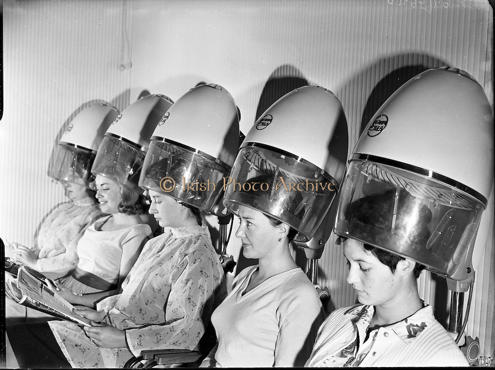 Being 'beautified' at the Jewel Hair Salon. Before the days of the 'blow-dry', ladies stoically endure the heat and noise of these contraptions..26.07.1960