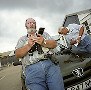Taking notes from an air band receiving radio, plane spotters log aircraft serial numbers and other details in notebooks near their perimeter fence at London's Heathrow airport. A large man has a pair of binoculars and an old SLR film camera and leans against his Peugeot car's bonnet (hood) to record the obsessive facts about airliners that pass overhead as they approach the runways of West London. His fellow-aviation enthusiast checks the radio that transmits the voices of pilots and air traffic controllers. In Britain, plane spotters are regarded as eccentric and sad but not trespassers. Some have been accused of spying near foreign military airfields. Picture from the 'Plane Pictures' project, a celebration of aviation aesthetics and flying culture, 100 years after the Wright brothers first 12 seconds/120 feet powered flight at Kitty Hawk,1903.