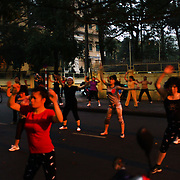 Women take part in an early morning keep fit class on the street in Hanoi, Vietnam.. For a county not know for it's sporting prowess, Hanoi, Vietnam's capital, appears to be gripped in a fitness frenzy. Before 6am street corners, parks and lake sides are a hive of activity as keep fit classes, Tai chi and personal exercise regimes are seen in abundance around the city. Particularly noticeable are Women's keep fit classes, often accompanied by loud poor quality western disco beat music as the occupants of the city get fit come rain or shine. Hanoi, Vietnam. 18th March 2012. Photo Tim Clayton
