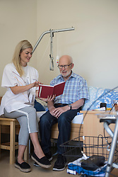 Nurse reading a book to senior man in rest home, Bavaria, Germany, Europe