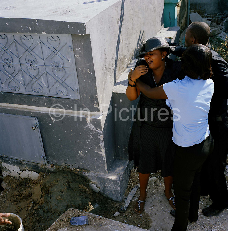 Chaumone Auguste  mourns the loss of her mother, Mereille Jeudy at the main cemetery in Port Au Prince. Mereille was sixty-four when she died.