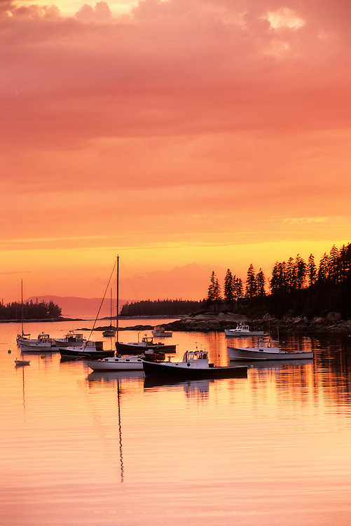 Deer Island, Maine.<br /> The little fishing village of Burnt Cove is towards the bottom of Deer Island in Maine.  The orange glow of sunset  after a hot day lent truth to the town's name, as it served as a backdrop for the lobster boats anchored for the night.