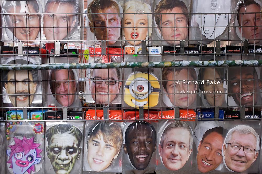 Detail of celebrity faces masks lined-up in a west end tourist shop rack