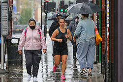 © Licensed to London News Pictures. 04/06/2021. London, UK. A runner jogging during rainfall in north London. According to The Met Office, more rain is expected today across London and the South East of England, with the hot weather returning tomorrow. Photo credit: Dinendra Haria/LNP