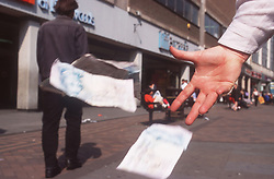 Closeup of adult's hand throwing money away in town centre,