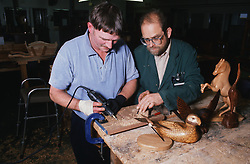 Male occupational therapist assisting patient with woodwork,