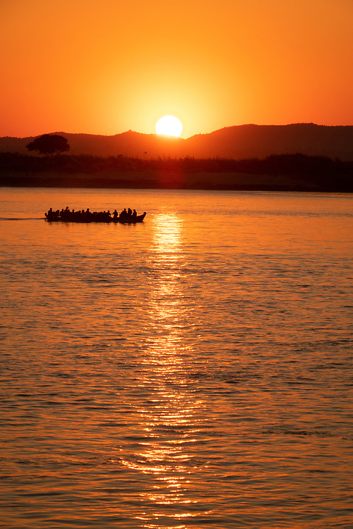 Photograph of a boat at sunset on the Irrawaddy River, Myanmar