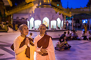 15 JUNE 2013 - YANGON, MYANMAR:  Buddhist nuns pray in the evening at  Shwedagon Pagoda. The Shwedagon Pagoda is officially known as Shwedagon Zedi Daw and is also called the Great Dagon Pagoda or the Golden Pagoda. It is a 99 metres (325 ft) tall pagoda and stupa located in Yangon, Burma. The pagoda lies to the west of on Singuttara Hill, and dominates the skyline of the city. It is the most sacred Buddhist pagoda in Myanmar and contains relics of the past four Buddhas enshrined: the staff of Kakusandha, the water filter of Koṇāgamana, a piece of the robe of Kassapa and eight strands of hair fromGautama, the historical Buddha. The pagoda was built between the 6th and 10th centuries by the Mon people, who used to dominate the area around what is now Yangon (Rangoon). The pagoda has been renovated numerous times through the centuries. Millions of Burmese and tens of thousands of tourists visit the pagoda every year, which is the most visited site in Yangon. PHOTO BY JACK KURTZ