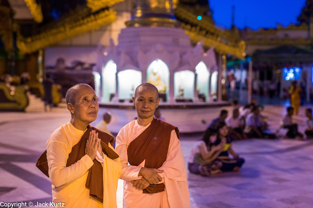 15 JUNE 2013 - YANGON, MYANMAR:  Buddhist nuns pray in the evening at  Shwedagon Pagoda. The Shwedagon Pagoda is officially known as Shwedagon Zedi Daw and is also called the Great Dagon Pagoda or the Golden Pagoda. It is a 99 metres (325ft) tall pagoda and stupa located in Yangon, Burma. The pagoda lies to the west of on Singuttara Hill, and dominates the skyline of the city. It is the most sacred Buddhist pagoda in Myanmar and contains relics of the past four Buddhas enshrined: the staff of Kakusandha, the water filter of Koṇāgamana, a piece of the robe of Kassapa and eight strands of hair fromGautama, the historical Buddha. The pagoda was built between the 6th and 10th centuries by the Mon people, who used to dominate the area around what is now Yangon (Rangoon). The pagoda has been renovated numerous times through the centuries. Millions of Burmese and tens of thousands of tourists visit the pagoda every year, which is the most visited site in Yangon. PHOTO BY JACK KURTZ