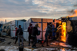 October 26, 2016 - Calais, France - Migrants and Volunteers extinguish in the Calais Jungle a burning hut in Calais, France on 26 October 2016. Huge fires destroyed a mayor part of the refugee camp today. (Credit Image: © Markus Heine/NurPhoto via ZUMA Press)