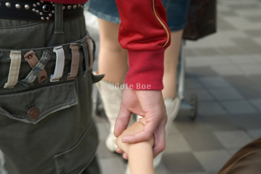 young father holding hand of a little child while walking