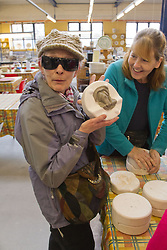 Visually impaired people with carers on outing to Denby Pottery. Woman with volunteer. Moulding clay into frog shape.