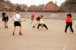 Secondary school pupils playing game of hockey on artificial pitch,
