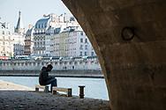 A man sits alone beside the Pont Neuf on the Île de la Cité in Paris, France