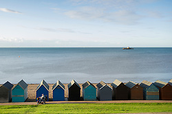 An old man drives past the beach huts on his mobility scooter with the remains of the old pier on the horizon, Herne Bay, Kent, England, United Kingdom.