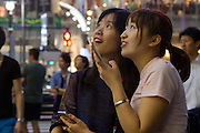 Two Young wome tourists China look in wonder at the bright lights of Shibuya Crossing, Shibuya, Tokyo, Japan. Friday, July 15th 2016