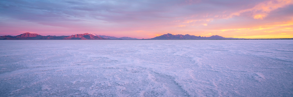 The expanse of the Bonneville Salt Flats spreads out towards the outcropping mountain peaks in the distance as the morning sun illuminates the sky.