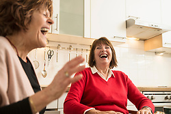 Two senior women talking and laughing in kitchen, Munich, Bavaria, Germany