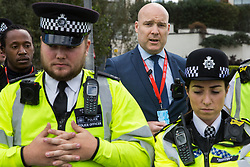 London, UK. 3 September, 2019. A representative of ExCel London (c), speaking inside a police cordon, reads a statement advising human rights activists taking part in protests outside the Abu Dhabi-owned exhibition centre against the DSEI arms fair that they are preventing a lawful activity. The second day's events were organised around a theme of No Faith In War and were attended by representatives of many faith groups including a significant number of Quakers.