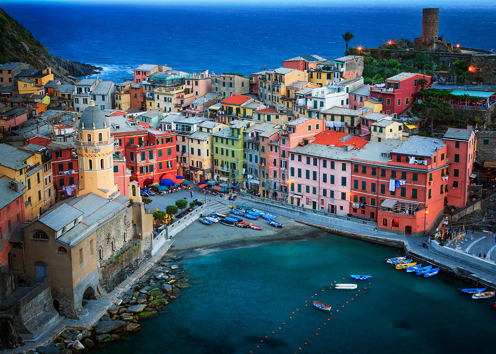 """Vernazza is a town and comune located in the province of La Spezia, Liguria, northwestern Italy. It is one of the five towns that make up the Cinque Terre region. Vernazza is the fourth town heading north, has no car traffic, and remains one of the truest """"fishing villages"""" on the Italian Riviera. Vernazza's name is derived from the Latin adjective verna meaning """"native"""" and the aptly named indigenous wine, vernaccia (""""local"""" or """"ours""""), helped give birth to the village's moniker. First records recognizing Vernazza as a fortified town date back to the year 1080. Referred to as an active maritime base of the Obertenghi, a family of Italian nobility, it was a likely point of departure for naval forces in defence of pirates. Over the next two centuries, Vernazza was vital in Genova's conquest of Liguria, providing port, fleet, and soldiers. In 1209, the approximately 90 most powerful families of Vernazza pledged their allegiance to the republic of Genova.In 1997, the Cinque Terre was recognized as a World Heritage Site by UNESCO and in 1999 the National Park of the Cinque Terre was born. Today the main source of revenue for Vernazza is tourism. However, as a testimony to the strength of centuries-old tradition, fishing, wine and olive oil production still continue to take place."""
