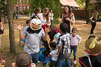 DEU, Deutschland, Germany, Berlin, 19.08.2015: Freiwillige Helfer der Initiative Moabit Hilft verteilen gespendete Kostüme an Flüchtlingskinder auf dem Gelände des Landesamts für Gesundheit und Soziales (LaGeSo), hier befindet sich die Zentrale Aufnahmeeinrichtung des Landes Berlin für Asylbewerber.
