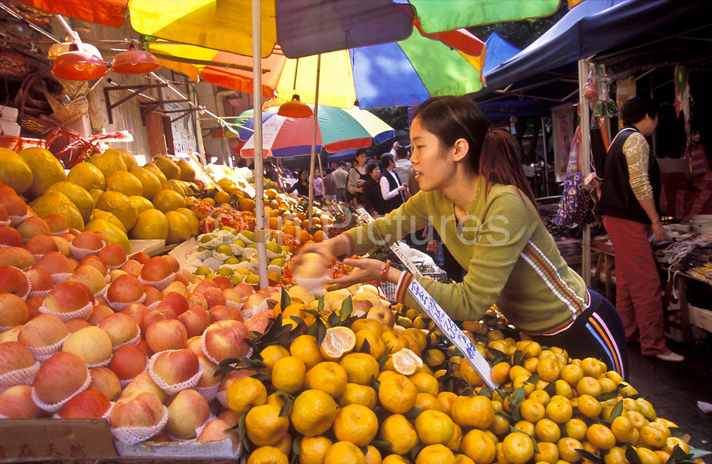 A women market stall fruit and vegetable vendor attends to her produce, Guangzhou  city, China