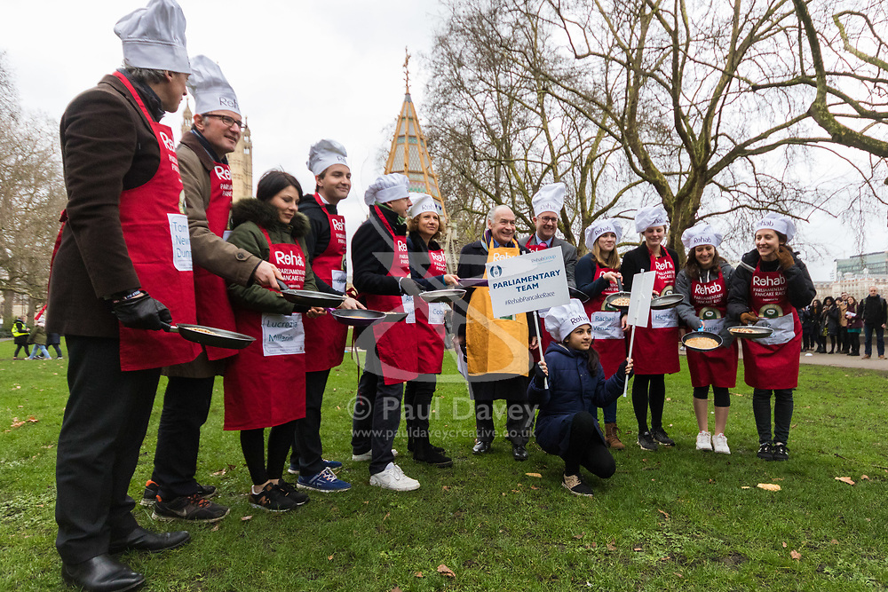 MPs and members of the House of Lords compete in the annual Rehab pancake race, a relay of eleven laps in Victoria Tower Gardens adjacent to the Houses of Parliament in London. The race is held every year on Shrove Tuesday and was won by the Media team. PICTURED: The Media Team pose for the press. London, February 13 2018.