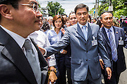 07 AUGUST 2013 - BANGKOK, THAILAND: Former Thai Prime Minister ABHISIT VEJJAJIVA, center right, walks with members of his party to the Thai Parliament building during anti-amnesty protests in Bangkok. Abhisit's party, the Democrats, organized the anti-amnesty protest. About 2,500 protestors opposed to an amnesty bill proposed by Thailand's ruling party marched towards the Thai parliament in the morning. The amnesty could allow exiled fugitive former Prime Minister Thaksin Shinawatra to return to Thailand. Thaksin's supporters are in favor of the bill but Thai Yellow Shirts and government opponents are against the bill. Thai police deployed about more than 10,000 riot police and closed roads around the parliament. Although protest leaders called off the protest rather than confront police, a few people were arrested for assaulting police when they tried to break through police lines. Several police officers left the scene under medical care after they collapsed in the heat.    PHOTO BY JACK KURTZ